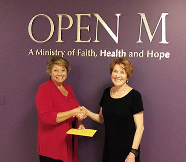 OPEN M CEO Dottie Achmoody accepts money raised by Gloria Rodgers for the 2016 Walk for OPEN M.